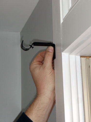 Screwing the three brackets into the wood trim: