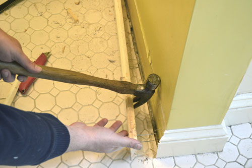 Carefully Prying Off Baseboards With Hammer Claw