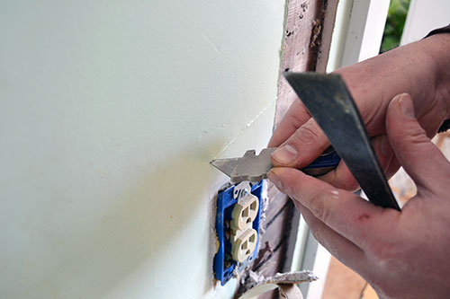 Carefully Cutting Sheet Rock Around Outlets