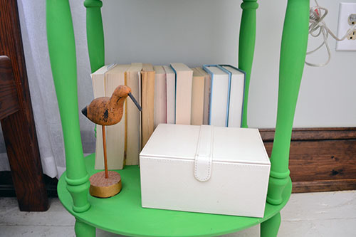 Nightstand Styling With Books And A Wooden Bird